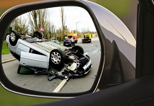 looking through a rear view mirror view at a car that has been in an accident